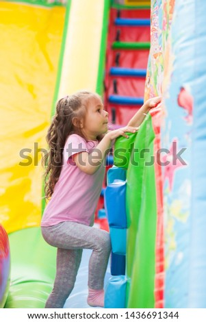 A cheerful child plays in an inflatable castle #1436691344