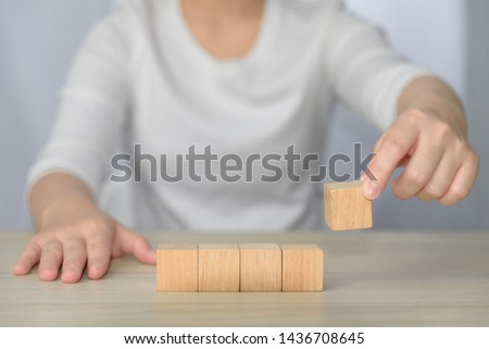woman hand arrange five blank wooden cube on table background. blank wood block for insert some sentence, icon, symbol, picture or meaningful word, idea and concept. #1436708645