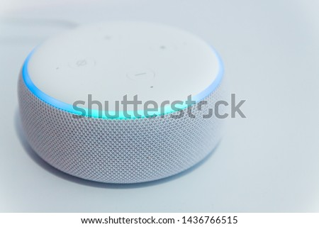 Amazon echo dot, voice controlled speaker with activated voice recognition, on light background. #1436766515