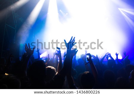 Stage lights and crowd of audience with hands raised at a music festival. Fans enjoying the party vibes. #1436800226