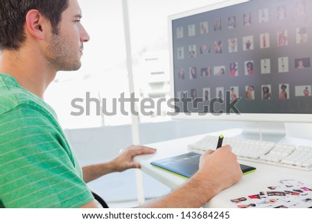 Concentrated photo editor working on graphics tablet at his desk