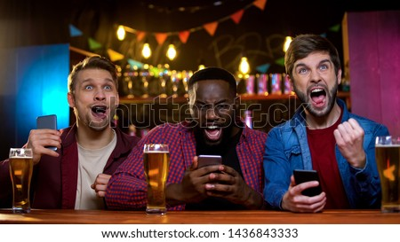 Excited friends rejoicing watching horse race and making bets online, income Royalty-Free Stock Photo #1436843333