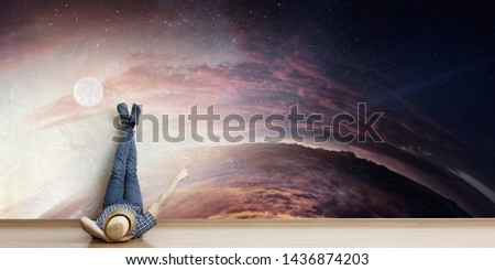 Young man lying on the floor with legs raised up on the wall. Mixed media #1436874203