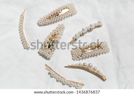 Group of White Pearl and Gold Hair Clips in Sunlight on White Background, Styled Shot Royalty-Free Stock Photo #1436876837