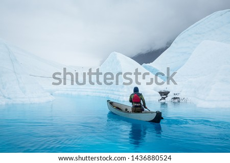 Man paddles a full size inflatable canoe across a deep blue glacier lake carved by water of the melting Matanuska Glacier in Alaska. #1436880524