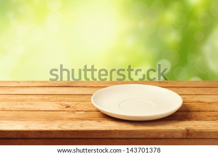 Empty plate on wooden table over bokeh background #143701378