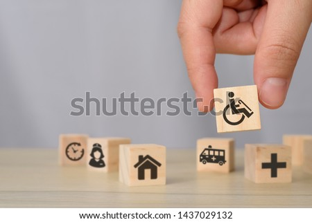 hand picking up wooden block with icons related to disability, medical, rehabilitation service, nursing care. can use for medical and rehabilitation concept article, banner, brochure in handicap. #1437029132