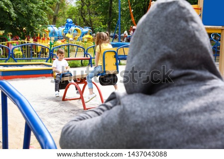 Suspicious adult man spying on kids at playground, space for text. Child in danger #1437043088