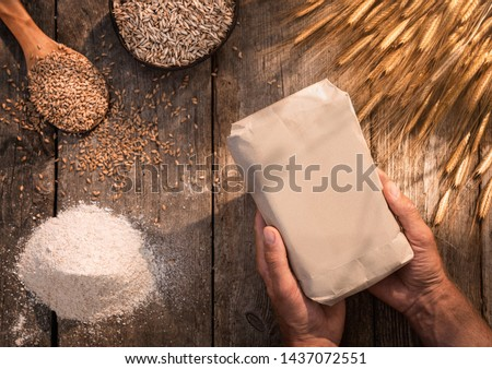 High angle view of male hands holding organic handmade eikorn flour over wooden table #1437072551