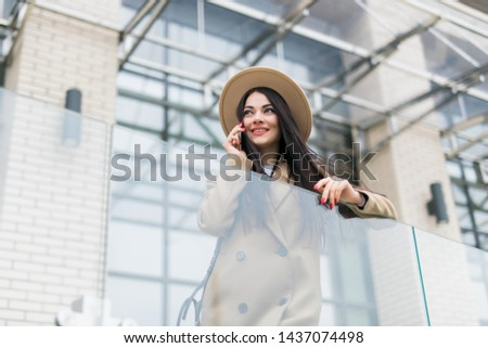 Caucasian business woman speaking by phone. Waist up portrait of a successful European business woman woman, talking on the phone, standing on glass background, modern office building. #1437074498