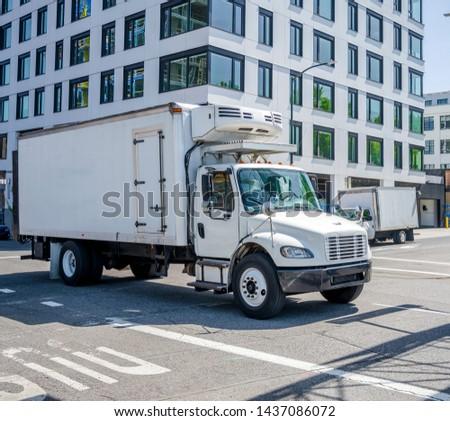 Small compact rig semi truck with refrigerator unit on box trailer transporting frozen and chilled foods on the street of urban city with multilevel buildings #1437086072