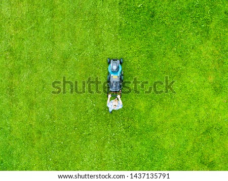 Beautiful girl cuts the lawn. Mowing lawns. Aerial view beautiful woman lawn mower on green grass. Mower grass equipment. Mowing gardener care work tool. Close up view. Aerial lawn mowing #1437135791