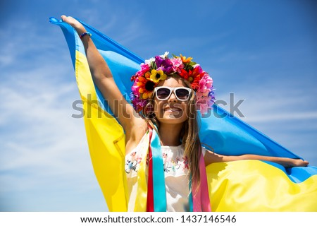 Happy Ukrainian girl carries fluttering blue and yellow flag of Ukraine against blue sky and sea background. Ukrainian flag is a symbol of independence. Celebrate Constitution day, Kyiv day, Kiev day #1437146546