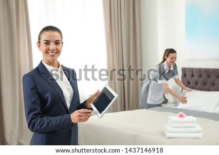 Housekeeping manager with tablet checking maid work in hotel room. Space for text #1437146918