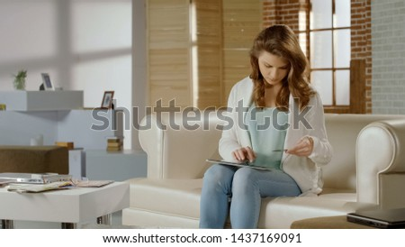 Young woman shopping online on tablet, using banking service to pay for purchase #1437169091