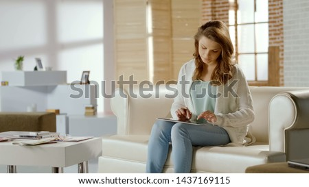 Female student working on project, using tablet at home, online education #1437169115