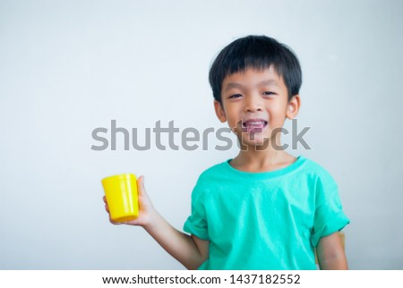 The boy holds a glass of yellow water on a white background. #1437182552