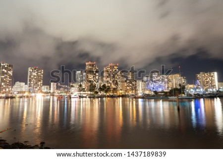 Cityscape of Honolulu at night on a cloudy day lights reflected in water #1437189839