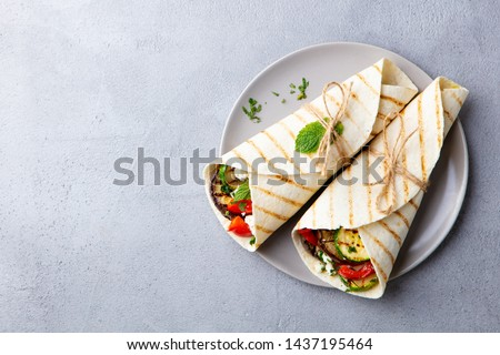 Wrap sandwich with grilled vegetables and feta cheese on a plate. Grey background. Copy space. Top view. #1437195464