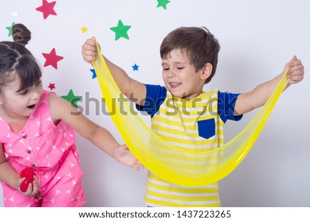 Kid playing hand made toy called slime. Children play with big yellow slime. Kid squeeze and stretching slime.  #1437223265