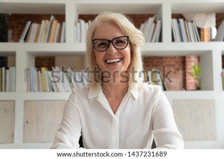 Happy old online teacher tutor look at camera give educational training class lecture teach by webcam, smiling mature business woman talk to webcam make video conference call sit at table in library #1437231689