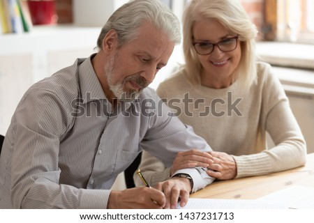 Happy older family couple husband and wife sign legal paper insurance contract write will testament, senior clients customers put signature on business document make financial deal take bank loan #1437231713