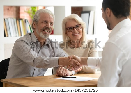 Happy senior old family couple clients make financial insurance estate business deal handshake agent lawyer, satisfied mature customers shake hand meeting bank manager agree on investment contract #1437231725