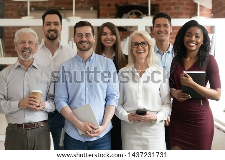 Happy diverse professional business team stand in office looking at camera, smiling young and old multiracial workers staff group pose together as human resource, corporate equality concept, portrait #1437231731