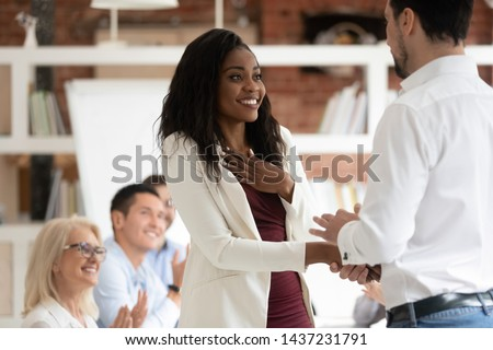 Happy black female employee get rewarded for professional achievement handshake boss, tolerant male manager shake hand of proud african business woman promote express recognition at work concept #1437231791