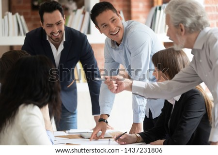 Happy diverse business team young and old employees talking brainstorming on project paperwork gather at conference table, smiling workers group engaged in teamwork at corporate briefing in boardroom #1437231806