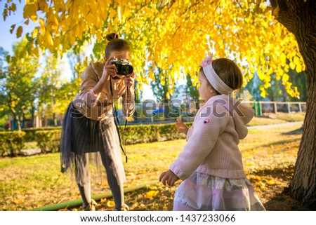 Girl with mom in autumn. Mom takes a picture of her daughter. Autumn photo shoot child. Mother photographer. Mother with her little daughter in the autumn park on a walk.