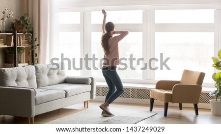 Overjoyed millennial girl have fun feeling happy entertaining in living room, excited young woman dancing alone at home, moving to the rhythm listening to music enjoy weekend. Stress free concept #1437249029