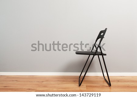 Side view of an empty black chair against a gray wall with a lot of copy space. #143729119