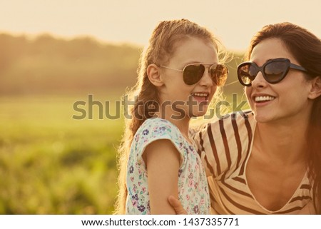 Happy fashion kid girl embracing her mother in trendy sunglasses in profile view and looking on nature background. Closeup portrait of happiness. #1437335771
