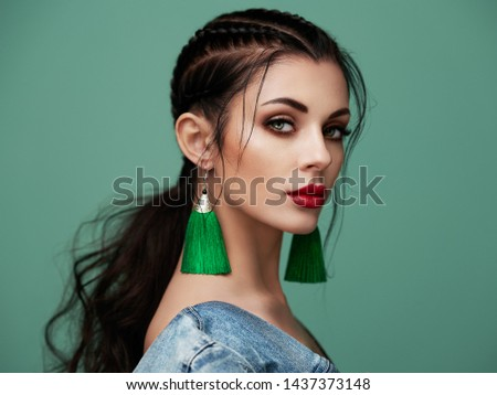 Brunette girl with perfect makeup. Beautiful model woman with curly hairstyle. Care and beauty hair products. Lady with braided hair. Model with jewelry. Turquoise background #1437373148