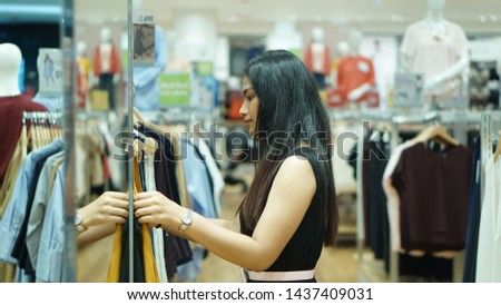 Portrait of a young Asian Thai woman in casual wear (Black fashion dress) shopping for clothes in a clothing store. She choose clothes happily. #1437409031