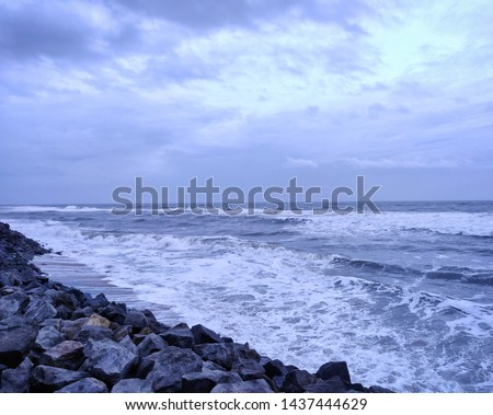 A picture of beach with rocks on the shore and cloudy sky on background. The sea is violent with strong waves in this picture.