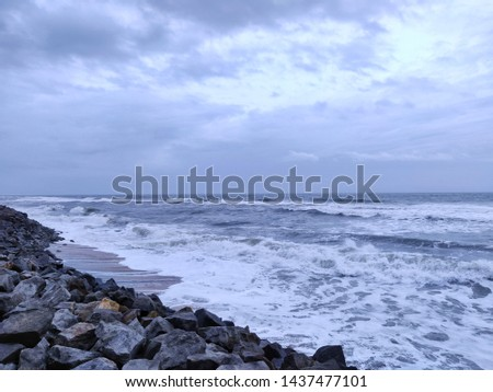 A picture of beach with rocks on the shore and cloudy sky on background. The sea is violent with strong waves in this picture. Kappil Beach (Varkala Town), Kerala.