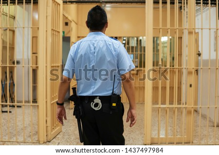 Jailer walking through the prison aisle, entering the safe zone. Prison officer in  blue shirt with handcuffs and a baton bypassing the corridor of a jail. #1437497984