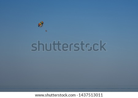 Multi-colored parachute over the sea on a background of the clear blue sky. #1437513011