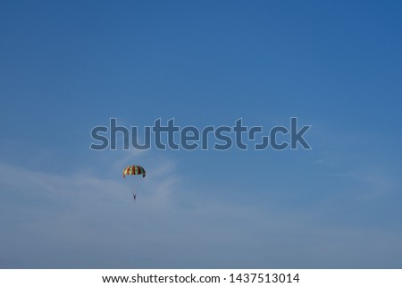 Multi-colored parachute over the sea on a background of the clear blue sky. #1437513014