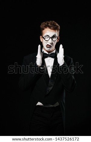 portrait of mime man in tuxedo and glasses on black background #1437526172