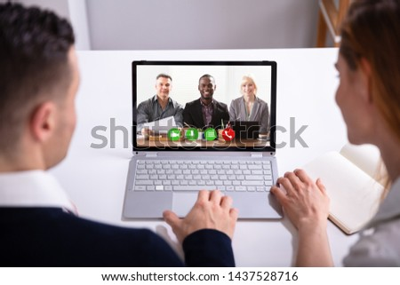 Rear View Of Businesspeople Video Conferencing With Their Colleagues On Laptop Over White Desk #1437528716