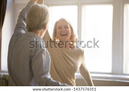 Happy middle aged mature woman enjoying dancing with elder husband at home, active healthy senior old couple man and woman pensioners having fun in waltz laughing bonding celebrating anniversary #1437576311