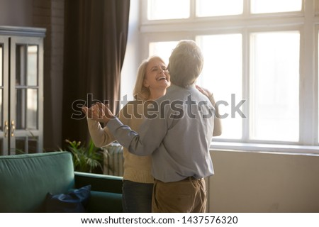 Cheerful retired spouses husband and wife laughing dancing in living room, happy romantic old middle aged couple enjoying slow dance having fun celebrating anniversary or new house purchase at home #1437576320