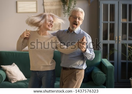 Carefree happy active old senior couple dancing jumping laughing in living room, cheerful retired elder husband holding hand of mature middle aged wife enjoy fun leisure retirement lifestyle at home #1437576323