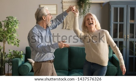 Joyful active old retired romantic couple dancing laughing in living room, happy middle aged wife and elder husband having fun at home, smiling senior family grandparents relaxing bonding together #1437576326