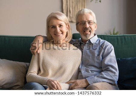 Happy retired old family couple looking at camera recording vlog, smiling senior spouses embracing doing distance video chat call talking to webcam sitting on sofa at home, webcamera view, portrait