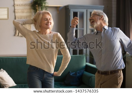 Happy active positive retired elder couple dancing together in living room, cheerful old senior husband and mature middle aged fit wife enjoying fun leisure activity laughing bonding moving at home #1437576335