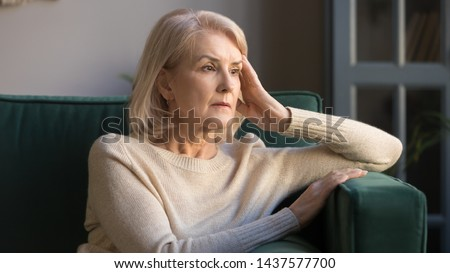 Pensive thoughtful middle aged lady looking away sit alone at home feel anxious lonely, sad depressed melancholic old mature woman suffer from sorrow grief thinking of problem suffer from solitude #1437577700